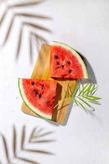 Lato w tle: plastry świeżego arbuza na białym tle z liści palmowych. flatlay, widok z góry.