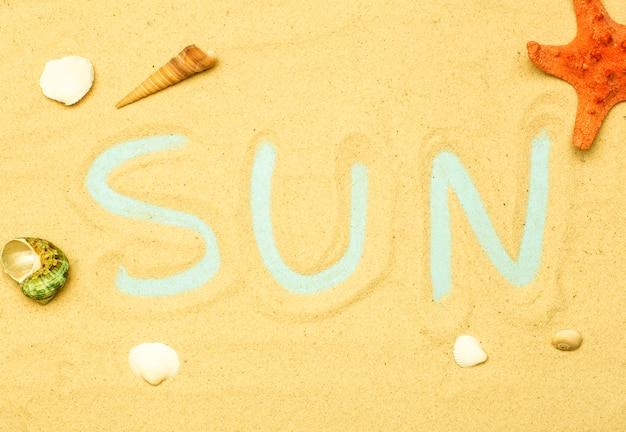 """Lato, wakacje na plaży na tle morza. napis i napis """"słońce"""" na piasku plaży w słoneczne letnie dni. morze, ocean i relaks w backgarund."""