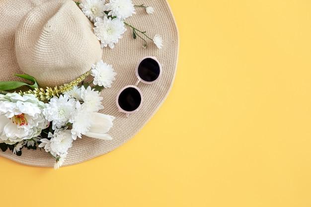 Lato z białymi kwiatami i wiklinową czapką z okularami przeciwsłonecznymi