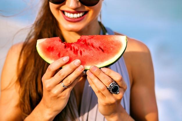 Lato z bliska szczegóły kobiety z ładnym uśmiechem trzymającej kawałek słodkiego smacznego arbuza, wegańskie jedzenie, doskonały posiłek na plaży.