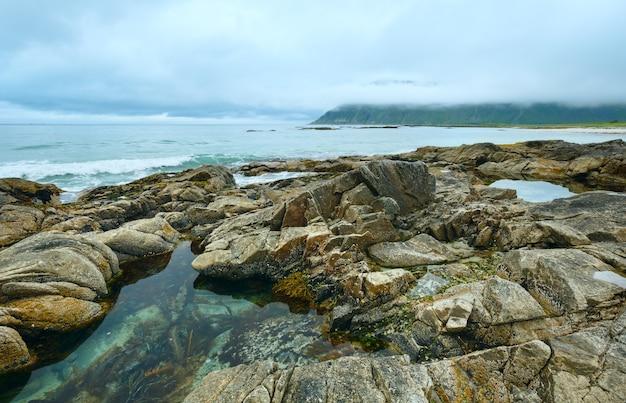 Lato zachmurzony widok na plażę z basenem w środku kamieni (ramberg, norwegia, lofoty).