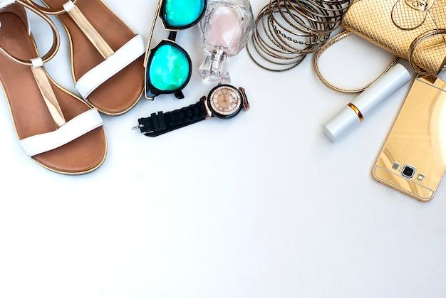 Lato żeńskich rzeczy biały drewniany tło.
