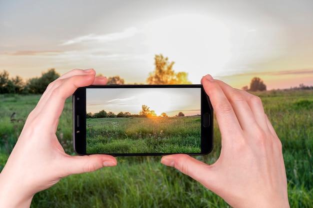 Lato zmierzch nad wiejskim polem. turysta robi zdjęcie