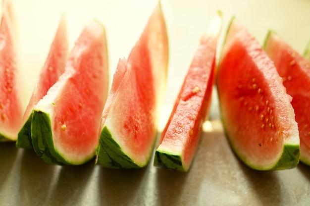 Lato żywności tło. dojrzałe plastry arbuza w talerzu, na ciepłym tle