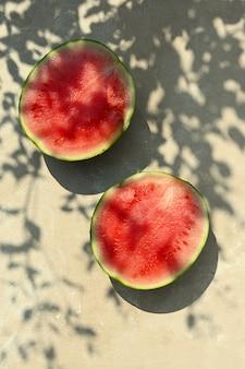 Lato żywności tło. dojrzały arbuz na ciepłym tle z twardymi odcieniami i światłem słonecznym.