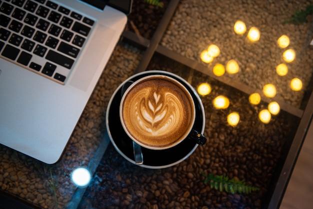 Latte art kawa w czarnej filiżance z laptopem i bokeh świateł na stole, ciemny odcień