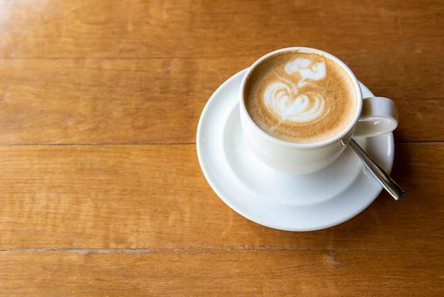 Latte art (kształt serca) na drewnianym stole z miejsca na kopię