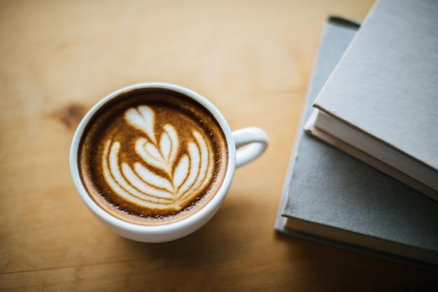 Latte art w filiżance kawy na stoliku kawiarnianym