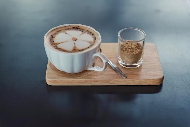 Latte sztuki kawa na białej filiżance gorącej kawy na drewnianej tacy i ciemnym stole.