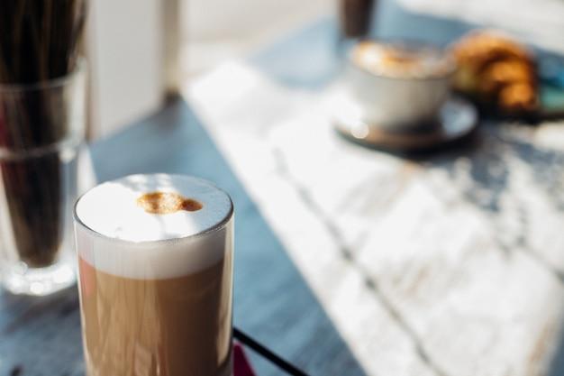 Latte w wysokiej szklance na rozmytym tle. napój leży na stoliku w kawiarni. pyszne śniadanie i przekąska. przyjemny wypoczynek i rekreacja.