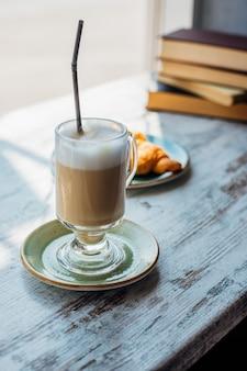 Latte w wysokiej szklance na tle stosu książek. napój leży na stoliku w kawiarni, obok rogalika. pyszne śniadanie i przekąska. przyjemny wypoczynek i rekreacja.