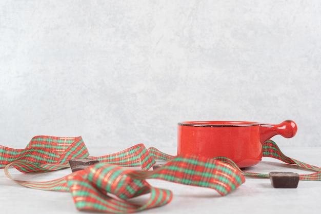 Latte, wstążka i kawałki czekolady na marmurowej powierzchni