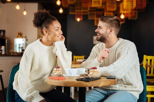 Latte z deserem. młoda, rozpromieniona para czuje się zrelaksowana i odprężona, delektując się poranną latte z deserem