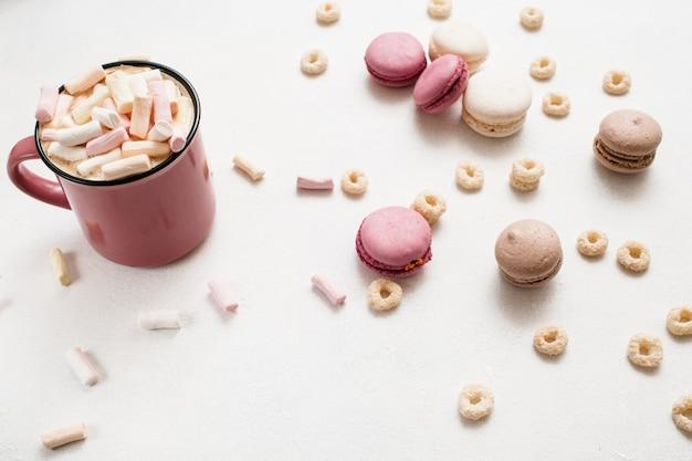 Latte z makaronikami. gorący napój z pianką i kolorowymi słodyczami