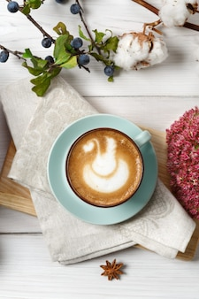 Latte z przyprawą dyniową. niebieska filiżanka z kremową pianką, jesiennymi suszonymi kwiatami, tarniną i bawełną. upadek gorące napoje, koncepcja oferty sezonowej, widok z góry, obraz pionowy