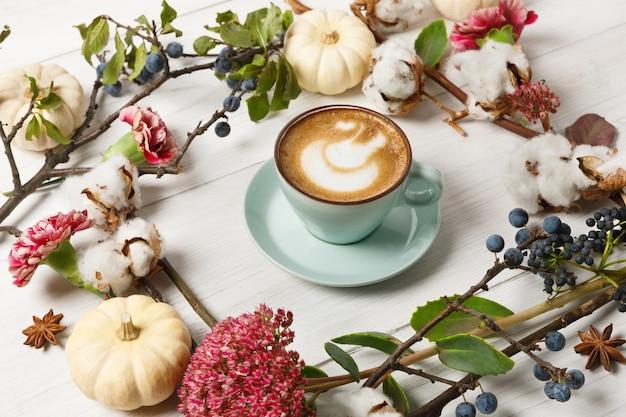 Latte z przyprawą dyniową. niebieska filiżanka z kremową pianką, jesiennymi suszonymi kwiatami, tarniną i małymi żółtymi dyniami. jesienne gorące napoje, koncepcja oferty sezonowej