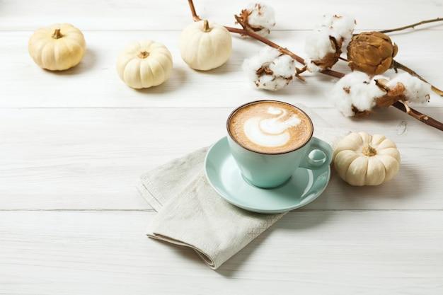 Latte z przyprawą dyniową. niebieska filiżanka z kremową pianką, laskami cynamonu, jesienną tarniną i małymi żółtymi dyniami. spadek koncepcji gorących napojów, kawiarni i baru