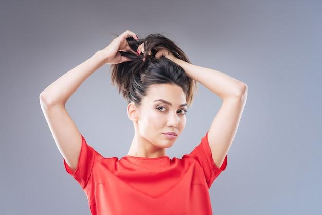 Łatwa fryzura. całkiem wesoła młoda kobieta w ładnej czerwonej sukience patrząc na swoje odbicie w lustrze, próbując zmienić fryzurę