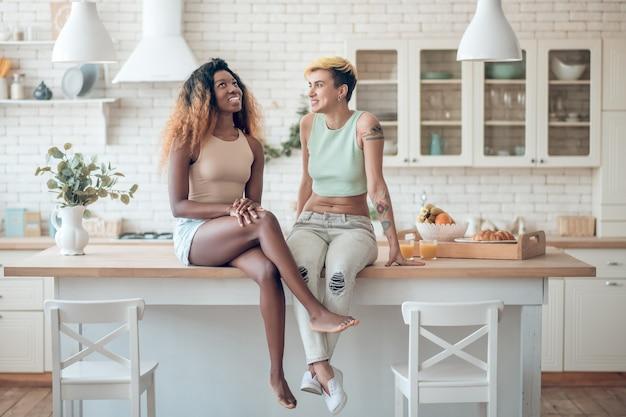 Łatwa komunikacja. dwie młode, dorosłe kobiety uśmiechnięte w ubranie siedzi na stole w kuchni, rozmawiając przyjemnie