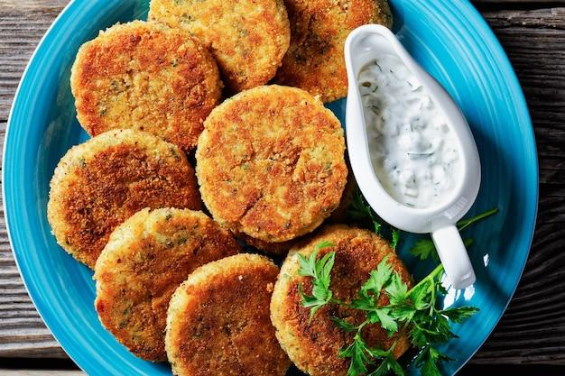 Łatwe placki rybne z fileta z białej ryby: dorsz lub plamiak z ziemniakami i pietruszką panierowane w bułce tartej podawane na talerzu z sosem tatarskim w sosjerce na drewnianym tle, widok z góry, zbliżenie