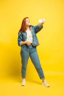 Łatwiej jest być naśladowcą. potrzebujesz minimum ubrań do selfie. portret kobiety kaukaski na żółtym tle. piękne kobiece włosy model. pojęcie ludzkich emocji, wyraz twarzy, sprzedaż, reklama.