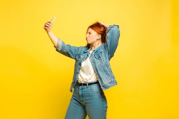 Łatwiej jest być naśladowcą. potrzebujesz minimum ubrań do selfie. portret kobiety kaukaski na żółtym tle. piękne kobiece włosy modelka. pojęcie ludzkich emocji, wyraz twarzy, sprzedaż, reklama.