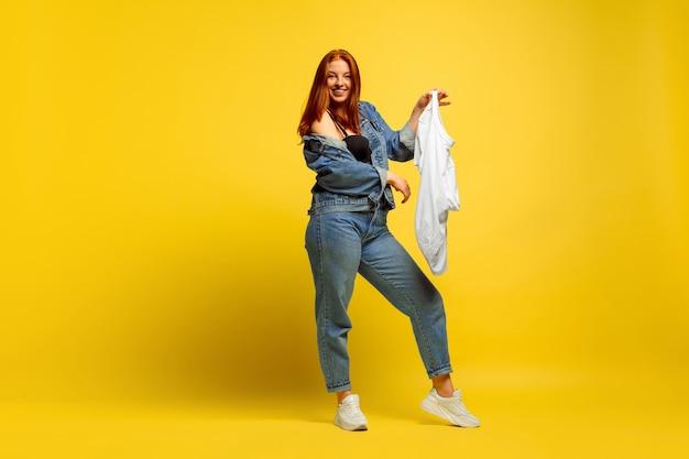 Łatwiej jest być naśladowcą. pranie szybciej, jeśli to tylko jedna koszula. portret kobiety kaukaski na żółtym tle. piękny model rudych włosów. pojęcie ludzkich emocji, wyraz twarzy, sprzedaż, reklama.