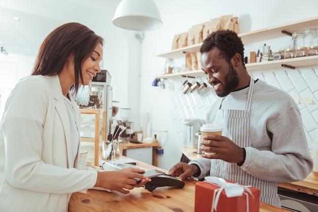 Łatwo i szybko. miła klientka przykładająca telefon komórkowy do terminala karty kredytowej i dokonująca płatności za swoje zamówienie za pomocą technologii nfc