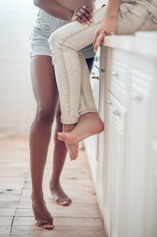 Łatwość. boso smukłe nogi stojącej ciemnoskórej kobiety w szortach i kaukaskiej dziewczyny w dżinsach siedzącej na stole