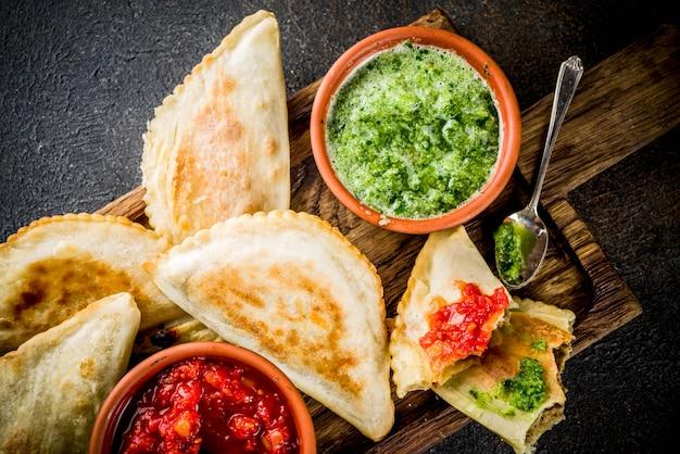 Latynoamerykańskie, meksykańskie, chilijskie jedzenie. tradycyjne empanady z pieczonego ciasta z mięsem wołowym, dwa pikantne sosy