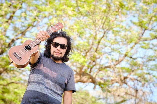 Latynos podnosi ukulele w środku lasu