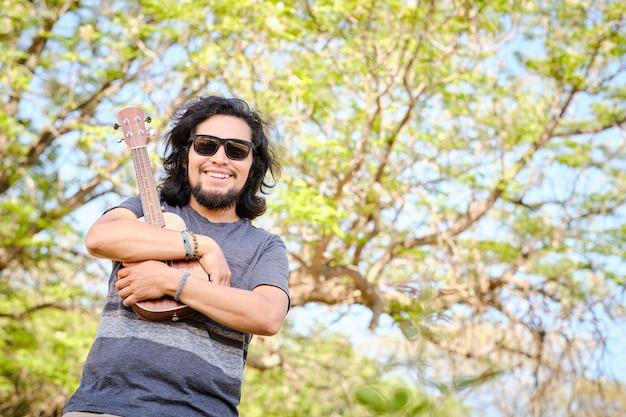 Latynos uśmiecha się, ściskając ukulele na środku łąki