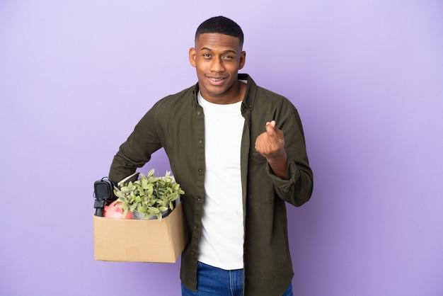Latynos wykonujący ruch podnoszący pudełko pełne rzeczy robiący gest pieniędzy
