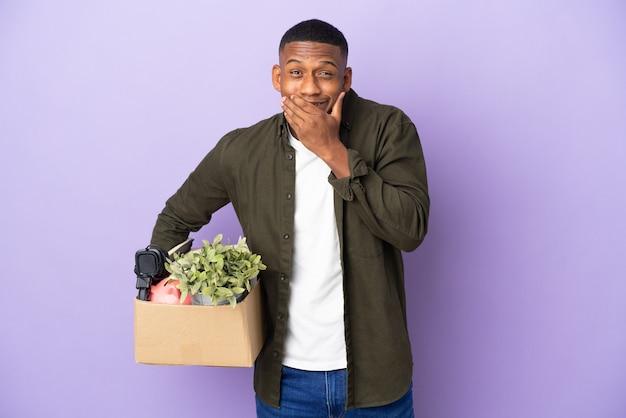 Latynos wykonujący ruch podnoszący pudełko pełne rzeczy szczęśliwy i uśmiechnięty, zakrywający usta ręką