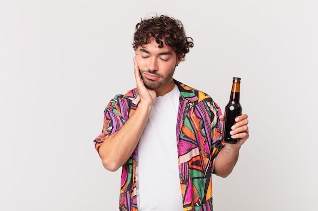 Latynos z piwem czuje się znudzony, sfrustrowany i senny po męczącym, nudnym i nudnym zadaniu, trzymając twarz ręką