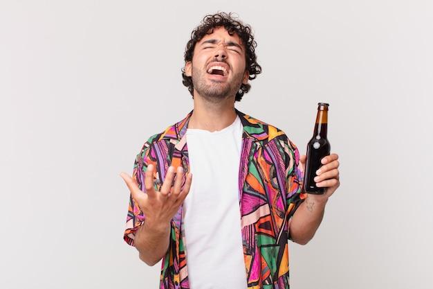 Latynos z piwem wyglądający na zdesperowanego i sfrustrowanego, zestresowanego, nieszczęśliwego i zirytowanego, krzyczącego i wrzeszczącego
