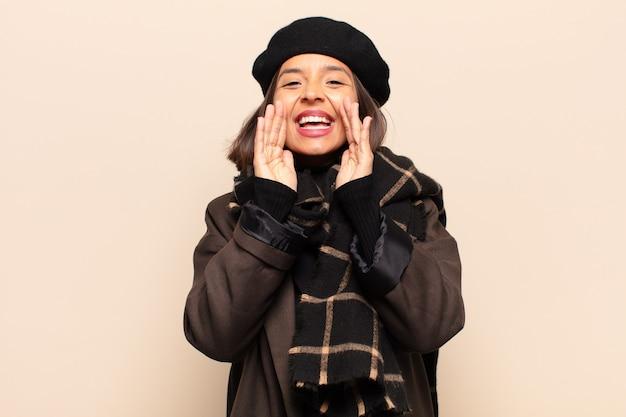 Latynoska kobieta czuje się szczęśliwa, podekscytowana i pozytywna, krzyczy głośno z rękami przy ustach i woła