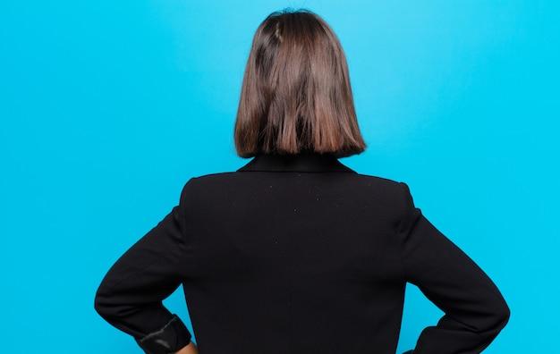 Latynoska kobieta czuje się zagubiona lub pełna lub ma wątpliwości i pytania, zastanawiając się, z rękami opartymi na biodrach, widok z tyłu