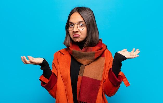 Latynoska kobieta czuje się zakłopotana i zdezorientowana, wątpi, waży lub wybiera różne opcje ze śmiesznym wyrazem twarzy