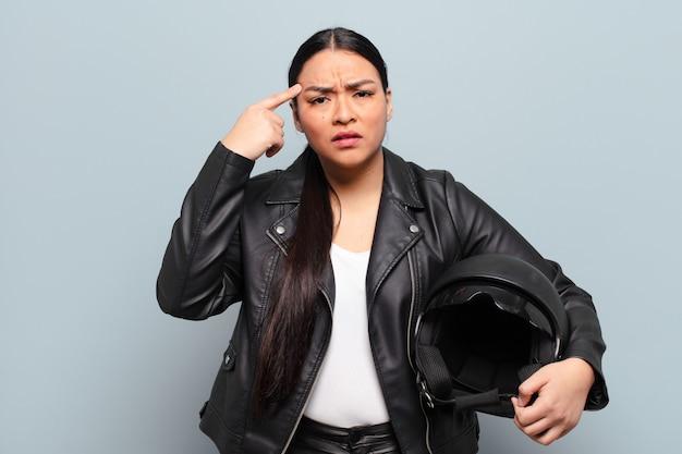 Latynoska kobieta czuje się zdezorientowana i zdziwiona, pokazując, że jesteś szalony, szalony lub oszalały