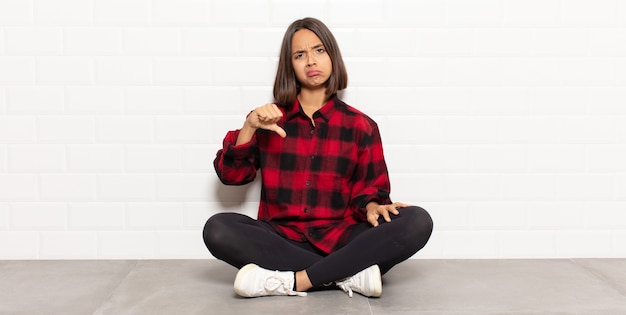 Latynoska kobieta czuje się zła, zła, zirytowana, rozczarowana lub niezadowolona, pokazuje kciuki w dół z poważnym spojrzeniem
