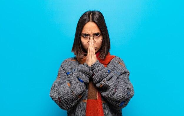 Latynoska kobieta czuje się zmartwiona, zdenerwowana i przestraszona, zakrywa usta rękami, wygląda na zaniepokojoną i popsuła