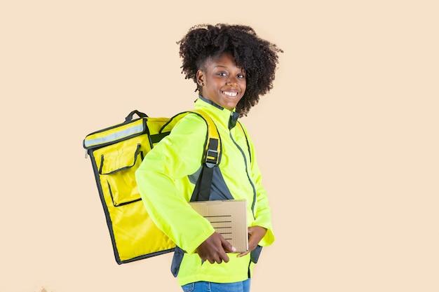 Latynoska kobieta dostarczająca paczki na beżowym tle