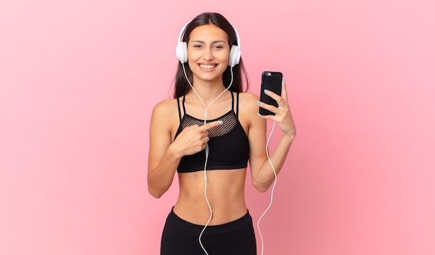 Latynoska kobieta fitness wyglądająca na podekscytowaną i zaskoczoną, wskazującą na bok ze słuchawkami i telefonem