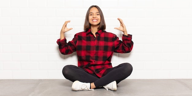 Latynoska kobieta kadrująca lub zarysowująca własny uśmiech obiema rękami, wyglądająca pozytywnie i szczęśliwie, koncepcja odnowy biologicznej