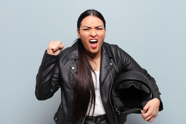 Latynoska kobieta krzyczy agresywnie z gniewnym wyrazem twarzy lub z zaciśniętymi pięściami świętując sukces