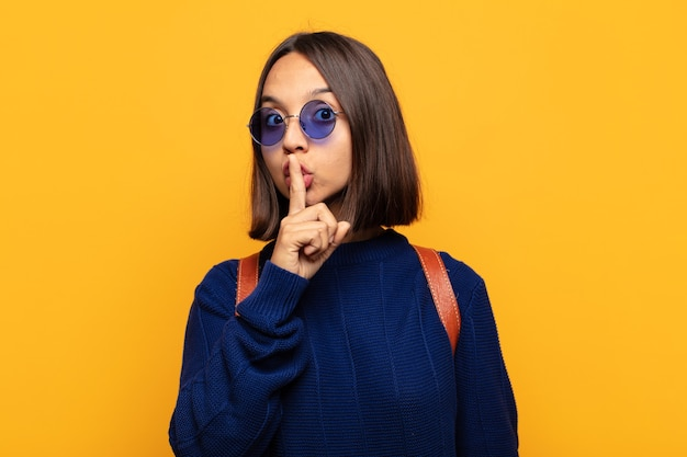 """Latynoska kobieta prosi o ciszę i spokój, gestykulując palcem przed ustami, mówiąc """"ciii"""" lub zachowując tajemnicę"""