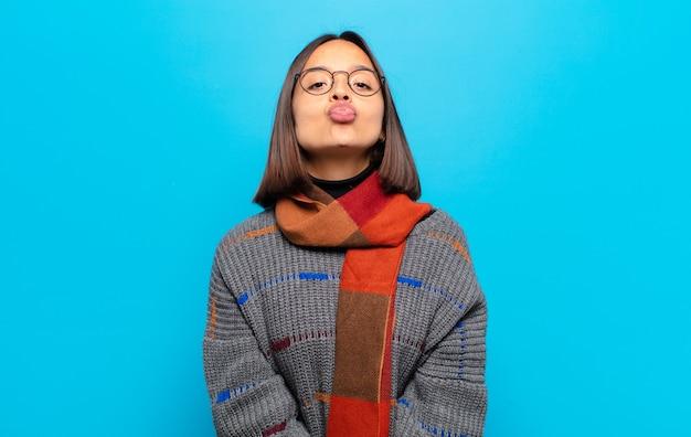 Latynoska kobieta ściskająca usta ze słodkim, wesołym, radosnym wyrazem twarzy, przesyłająca buziaka