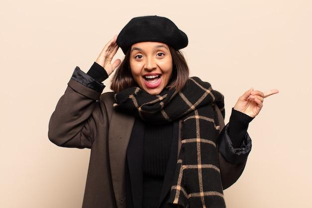 Latynoska kobieta śmiejąca się, wyglądająca na szczęśliwą, pozytywną i zaskoczoną, zdając sobie sprawę ze świetnego pomysłu wskazującego na boczną przestrzeń kopii