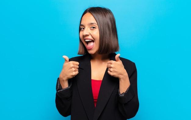 Latynoska kobieta, szeroko uśmiechnięta, szczęśliwa, pozytywna, pewna siebie i odnosząca sukcesy, z dwoma kciukami do góry